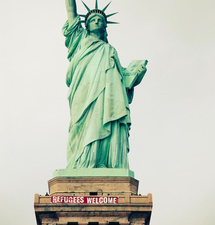 Banner reading 'Refugees Welcome' appears at base of Statue of Liberty