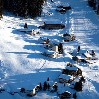 Skiers ski down a run and past chalets in the town of Davos, the location for the World Economic Forum's (WEF) 2012 annual meeting.
