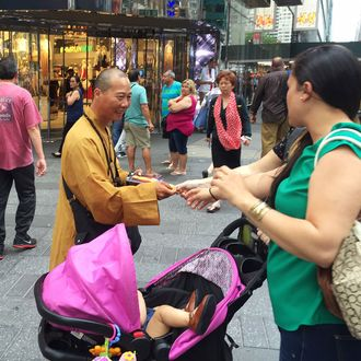In this June 23, 2016 photo, a man who says he is a Buddhist monk hands a medallion to a woman as he solicits donations on New York City's Times Square. Leaders of New York City's Buddhist community said that men in orange robes seeking donations near New York's popular tourist attractions are fakes, posing as monks to trick people into giving up their money. (AP Photo/Michael Balsamo)
