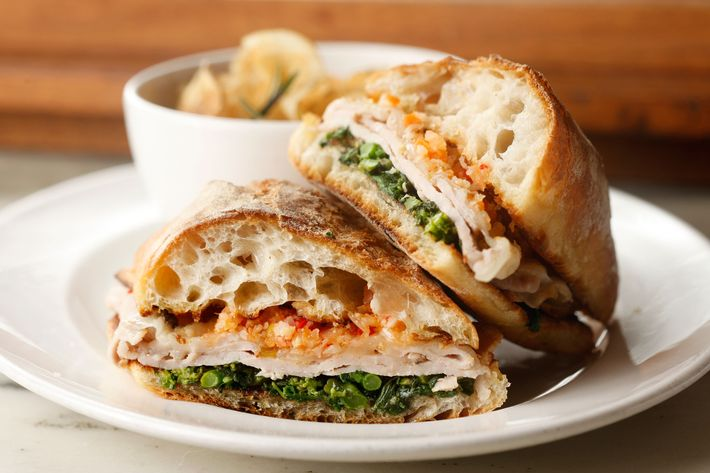Roast-pork sandwich with broccoli rabe, giardiniera, provolone, and chips.