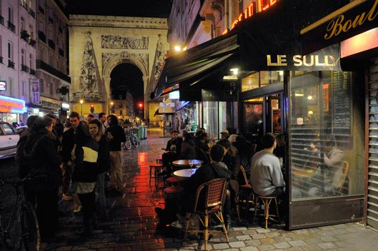 "Customers have a drink outside the bar ""Le Sully"" on October 4, 2012 on Rue Du Faubourg Saint-Denis in Paris."