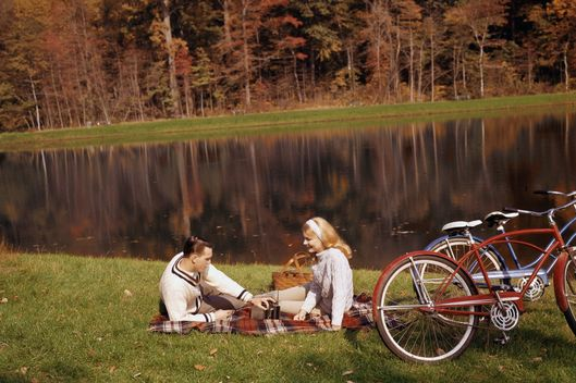 A man in a cricket sweater adjusts a transistor radio on a picnic blanket as a woman with a headband looks on and smiles, 1965. They are beside a small body of water and have a picnic basket and two bicycles.