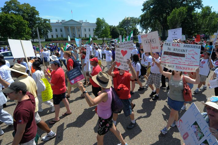"Teachers march past The White House during a ""Save Our Schools"" rally in Washington on July 30, 2011. In background is a anti-President Assad rally. Just across the street from The White House in Lafayette Park was a pro-President Assad rally. The two Assad rallies were chanting against each other until the ""Save Our Schools"" marchers passed. Then both Assad rallies cheered in favor of the teacher's rally."