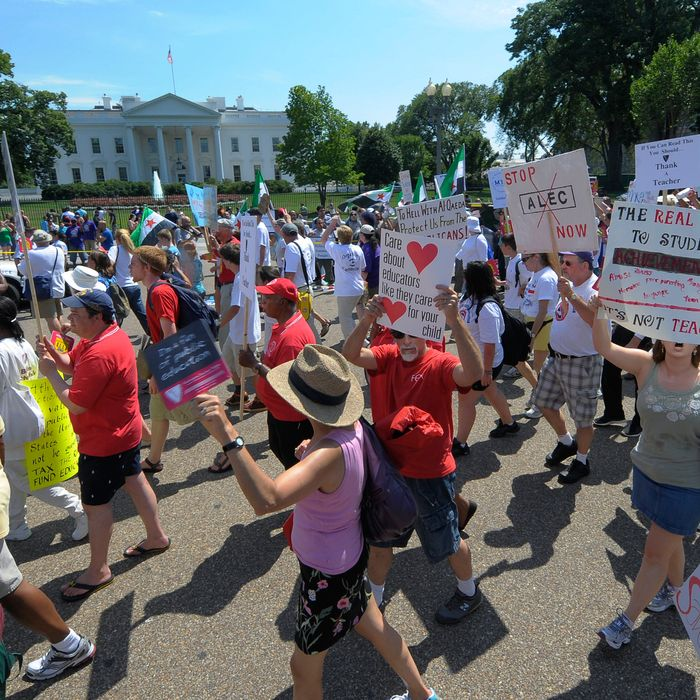 Teachers march past The White House during a