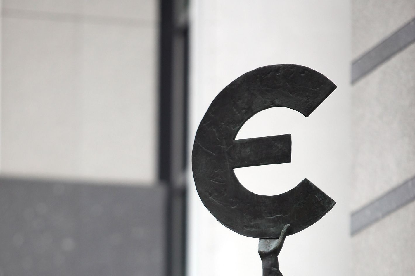 """The """"Europe"""" sculpture by Belgian artist May Claerhout, showing a woman holding up the symbol of the Euro, stands outside the European Parliament building."""