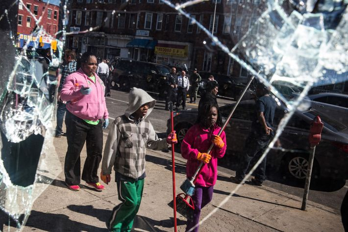BALTIMORE, MD - APRIL 28:  People helping to clean up debris caused by rioting yesterday after the funeral of Freddie Gray are seen in the reflection of a partially destroyed window on April 28, 2015 in Baltimore, Maryland. Gray, 25, was arrested for possessing a switch blade knife April 12 outside the Gilmor Houses housing project on Baltimore's west side. According to his attorney, Gray died a week later in the hospital from a severe spinal cord injury he received while in police custody.  (Photo by Andrew Burton/Getty Images)