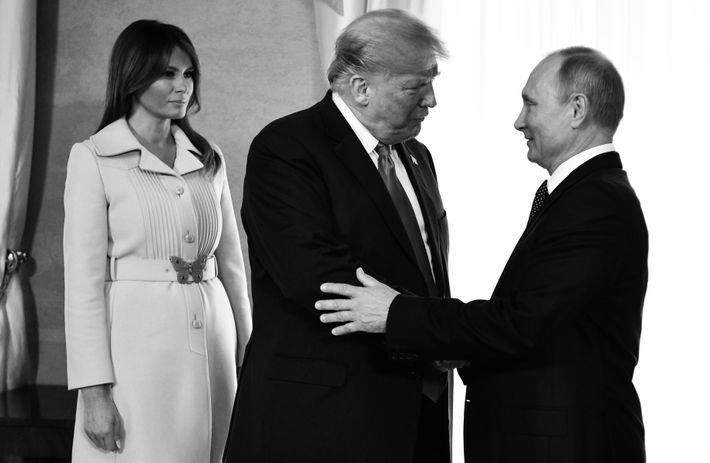 Melania Trump looks on as Donald Trump and Vladimir Putin shake hands.