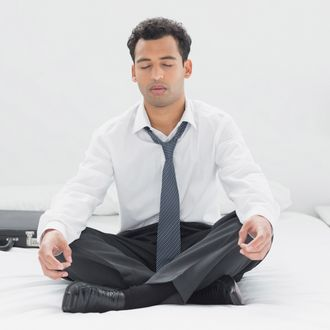 Relaxed young businessman sitting in lotus pose on bed