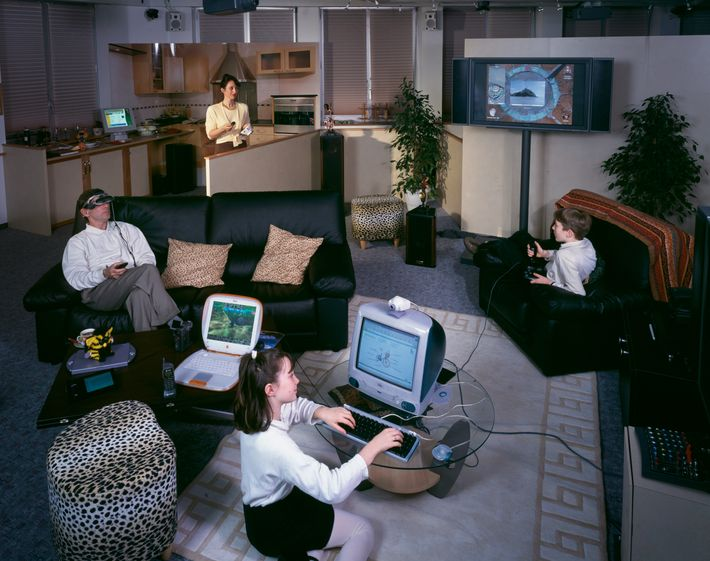 A family sits around a living room. Each person is looking at a computer.