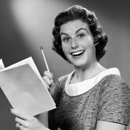 Portrait of woman smiling, holding up pencil & budget book. (Photo by H. Armstrong Roberts/Retrofile/Getty Images)