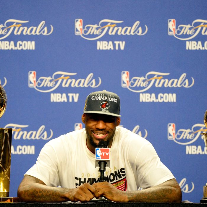 LeBron James #6 of the Miami Heat answers questions from the media next to the Larry O'Brien Finals Championship trophy and James' Bill Russell Finals MVP trophy during his post game press conference after they won 121-106 against the Oklahoma City Thunder in Game Five of the 2012 NBA Finals on June 21, 2012 at American Airlines Arena in Miami, Florida.