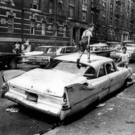 "Bronx, New York City, New York / Summer, 1966 On Fox Street in the Bronx, an abandoned Plymouth ""Savoy"" becomes a jungle gym for kids to play in and on."