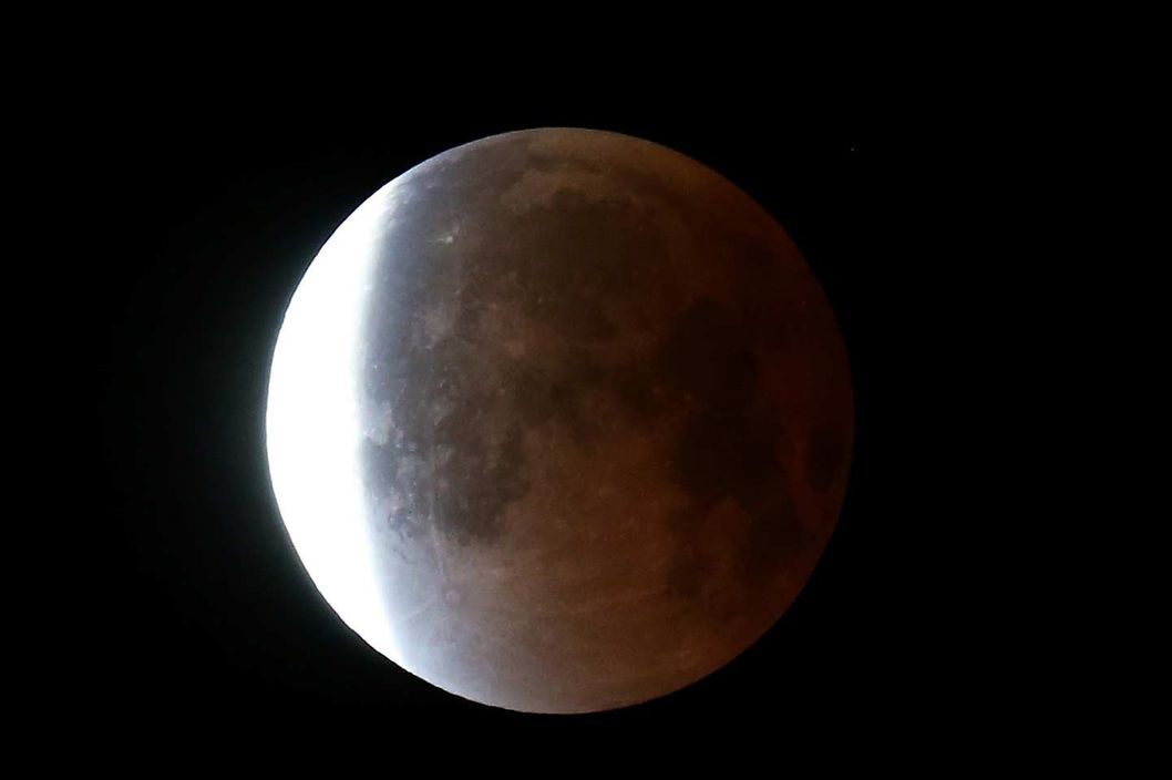 MIAMI, FL - APRIL 15:  The moon is seen as it emerges from a total lunar eclipse on April 15, 2014 in Miami, Florida. People in most of north and south America should be able to witness this year's first total lunar eclipse, which will cause a 'blood moon' and is the first of four in a rare Tetrad of eclipses over the next two years.  (Photo by Joe Raedle/Getty Images)