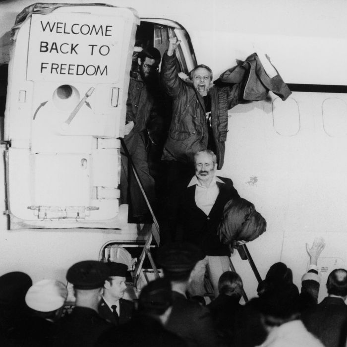 January 1981: United States hostages departing an airplane on their return from Iran after being held for 444 days. One of the hostages is waving his fists in the air, and a sign on the plane door says, 'Welcome Back to Freedom'.