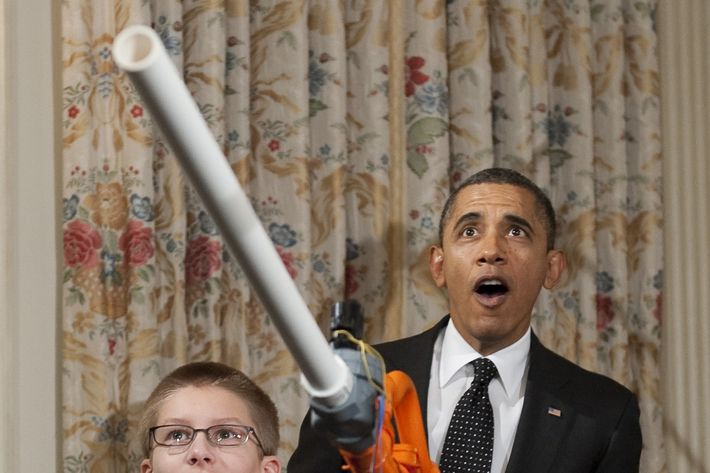 "US President Barack Obama reacts as 14-year-old Joey Hudy of Phoenix, Arizona, launches a marshmallow from Hudy's ""Extreme Marshmallow Cannon"" during a tour of the White House Science Fair in the State Dining Room of the White House in Washington, DC, February 7, 2012."